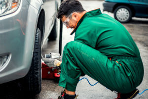 mechanic-green-overalls-changing-tire